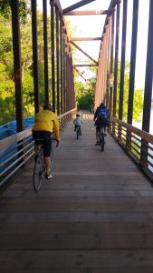 Bike to School days 2019 photo of cyclists riding over a small bridge along the Riverwalk.